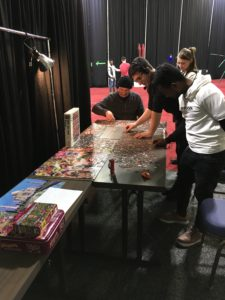 Cast and crew together work on a 1000 piece puzzle backstage.